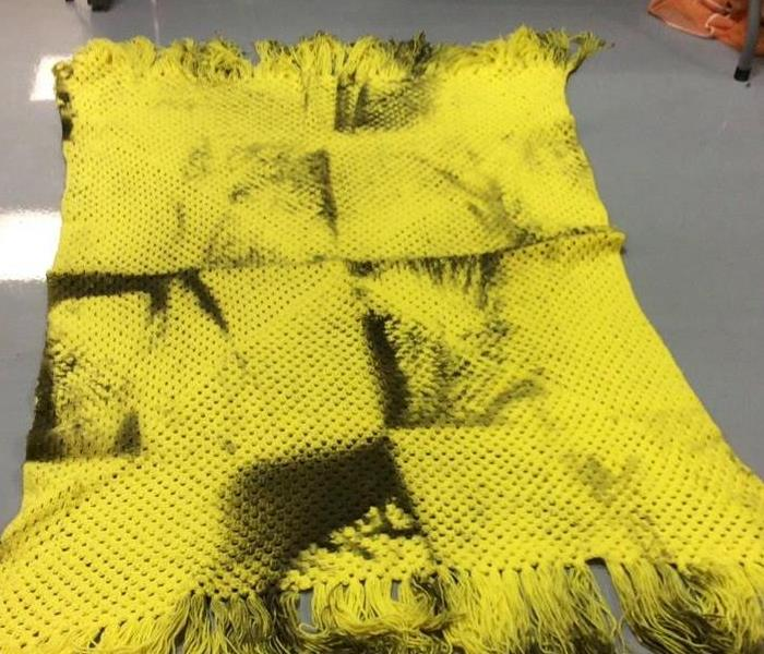 Yellow blanket with soot stains all over it from fire damage.