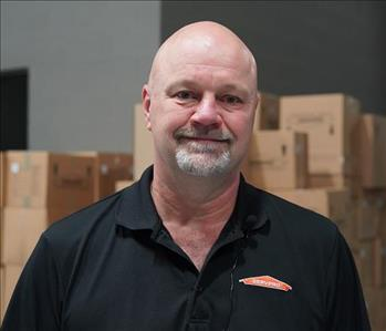 Bald man with SERVPRO shirt standing in front of boxes in a warehouse