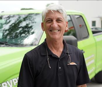 Man with grey hair in front of SERVPRO truck